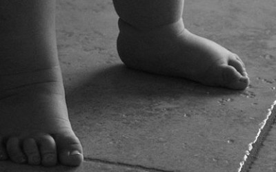 A black and white image of a baby's feet on a tiled floor