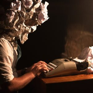 A person working at a typewriter, with balled up paper for a head