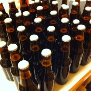 A table covered with brown beer bottles with white caps