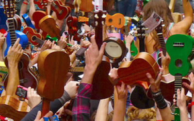 A crowd holding their ukuleles in the air