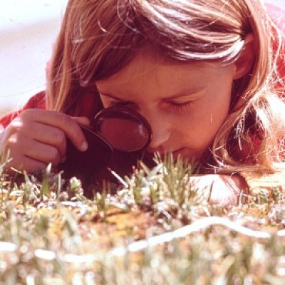 A girl looking at plants through a magnifying glass.