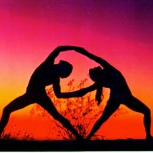 Two people silhouetted against an orange and pink sunset backdrop, in a yoga pose together