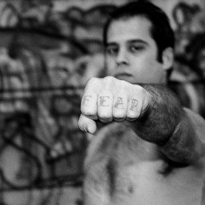 A man holding his fist towards the camera with the word 'fear' tattooed on his fingers