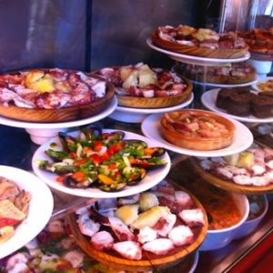 Plates of Spanish tapas in a restaurant window.