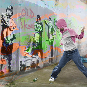 A person in a hoodie, dancing hip hop in front of 'old skool' graffiti