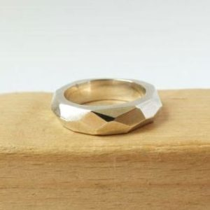 A shiny silver ring with an angular design