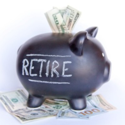 A piggy bank with the word 'retire' on it's side, stuffed with money