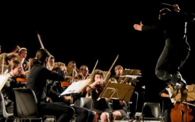 A conductor jumping in the air while leading an archestra