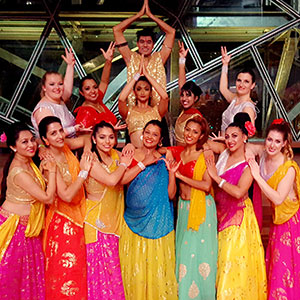 Bollywood dancers smiling and wearing bright clothing