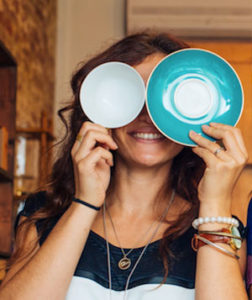 Sarah, holding up a cup and saucer in place of her eyes