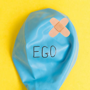 A deflated blue balloon with a plaster and the word 'ego' written on it