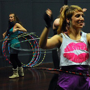 People smiling and dancing with hula hoops.