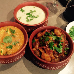 Three Indian dishes in terracotta bowls