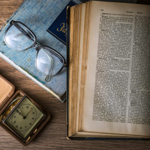 An old book and glasses on a table.