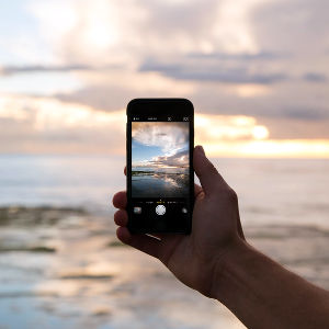 A beach sunrise being photographed on a smart phone