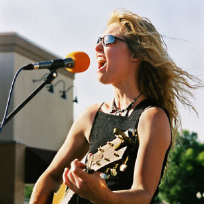 A woman performing at an outdoor event, singing into a microphone and playing guitar
