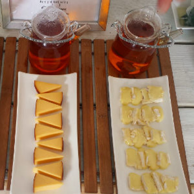 Two pots of tea in front of two different types of cheese