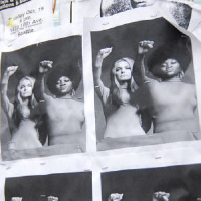 A black and white poster of two women standing with fists raised