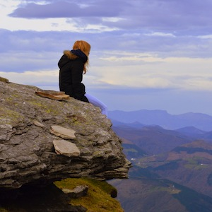 A person sat at the edge of the mountain enjoying the view