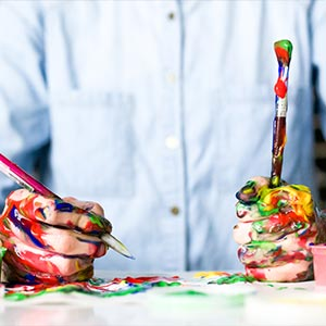 A person holding a paintbrush and pencil with many colours of paint covering their hands