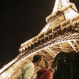 Lovers sharing a kiss underneath the Eiffel Tower