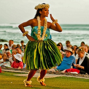 A Hawaiian hula dancer smiling and performing to a crowd next to a beach