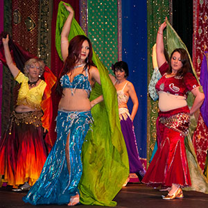 Four belly dancers performing on stage in bright colours