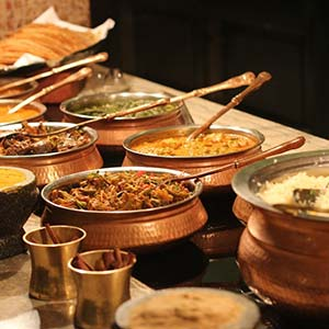 A table laid with different Indian dishes in bronze pots