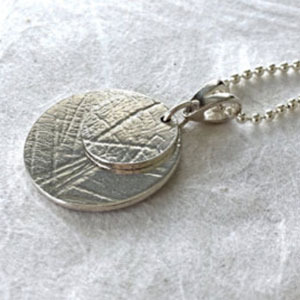 A solid silver pendant with a leaf pattern