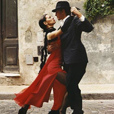 A man in a dark suit and a lady in a red dress dancing the tango in an Argentinian cobbled street