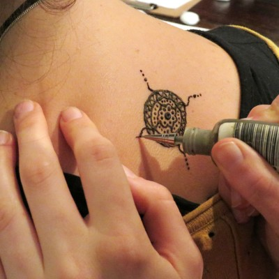 A student drawing a henna design on a friend.