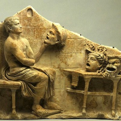 A relief with a seated figure holding a head or mask and two other heads on masks on a table