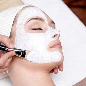 A woman receiving a facial mask at a salon