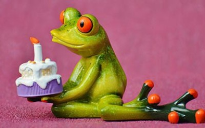 A frog figurine, holding a birthday cake