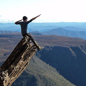 A person on top of a mountain with their arms raised in celebration