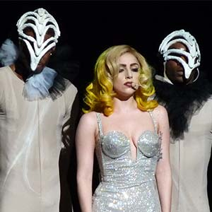 Lady Gaga on stage with two backing dancers