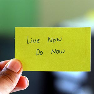 A hand holding up a note reading 'Live now, do now'
