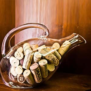 A wine carafe full of corks
