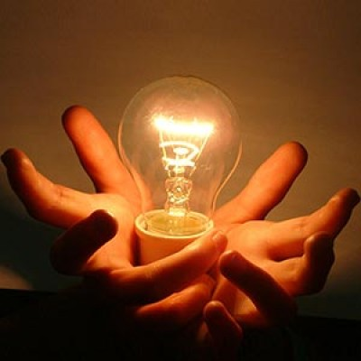 Two hands holding a glowing light bulb