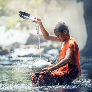 A young Buddhist monk uses water as a meditation tool