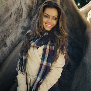 A smiling, beautiful woman in winter coat and scarf