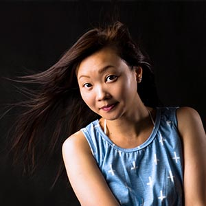 A woman smiling and posing for a photo with wind in her hair