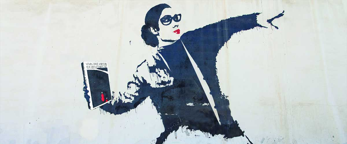 Banksy art showing a woman throwing an Atwood book like a weapon
