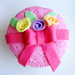 A cupcake decorated with a ribbon and roses