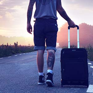 A man walking into a sunset with a small suitcase.