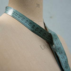 A dressmaker's mannequin with a tape measure around the neck