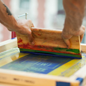 A person screen printing.