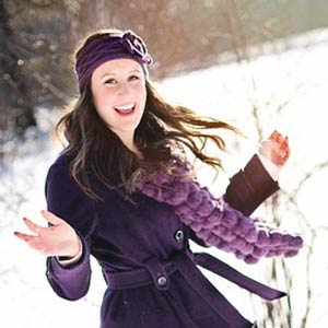 A woman smiling and dancing in the snow.