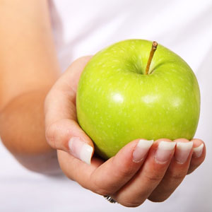 Someone holding a fresh, green apple.