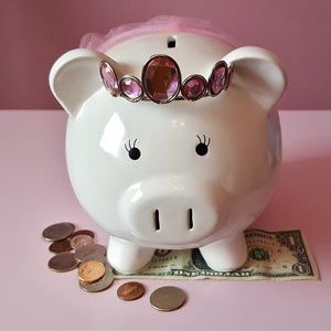A piggy bank with money at its feet.
